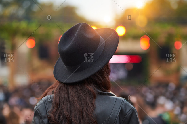 Back view of long haired fashion woman in black hat and leather jacket enjoying entertainment with people in park at festival in sunny day