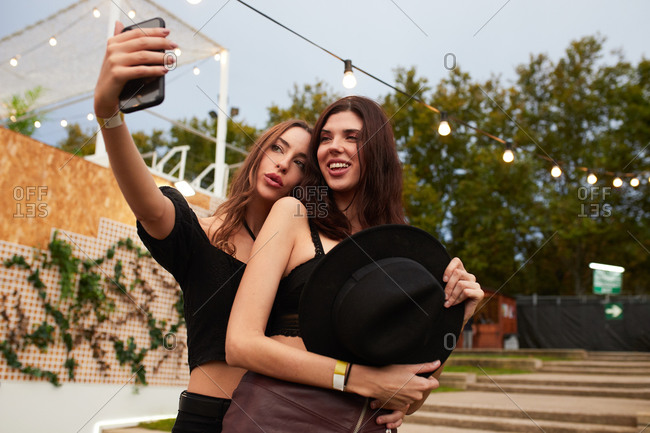 Stylish cheerful girl friends in black hat embracing and taking selfie on mobile phone in bright day at decorated arena on festival