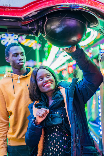 Happy black woman smiling and punching ball while playing arcade game with boyfriend at night on funfair