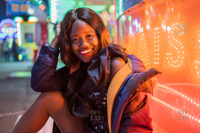 Optimistic African American female smiling and looking at camera while sitting near illuminated arcade in evening on fairground