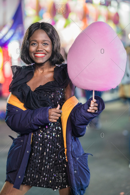 Optimistic black female with candy floss smiling and looking at camera while having fun on fairground at night