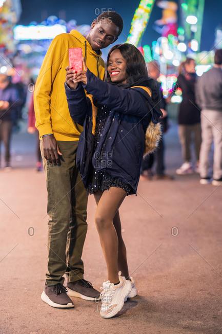 Black couple taking selfie on fairground