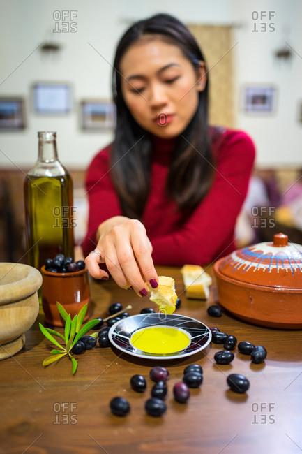 Thoughtful young Asian woman sitting and dipping bread in olive oil in plate on table with dishes and olives