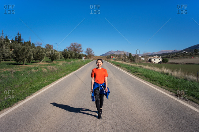 Charming Asian woman smiling and looking at camera while walking along road among fields in sunny day