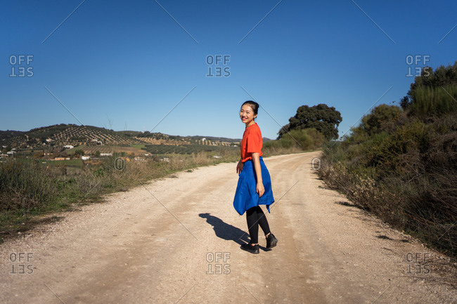 Charming Asian woman smiling and looking over shoulder while walking along road among fields in sunny day