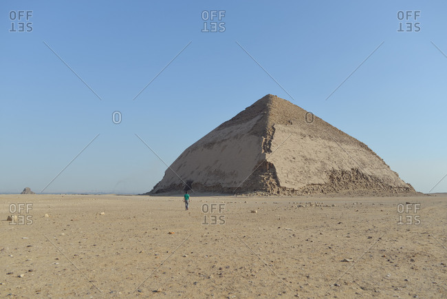 Cairo, Egypt - December 14, 2019: Traveler standing against ancient pyramid on sunny day landscape in sunny desert