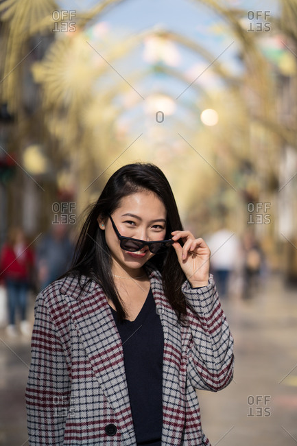 Charming Asian lady in casual clothes and sunglasses smiling at camera while standing on street against golden arches and blurred locals in city in Spain
