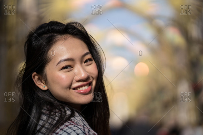 Happy ethnic young woman on street in downtown
