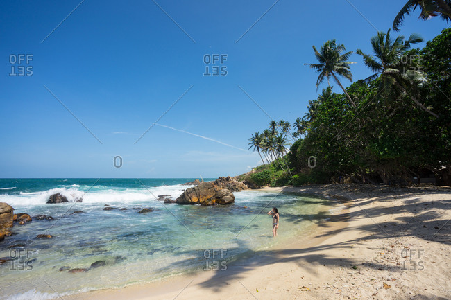 Lady in swimsuit resting on exotic lonely seashore