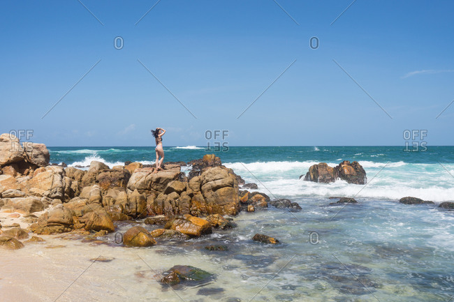 Young female tourist in bikini standing on rocks among turquoise ocean with blue sky on background on sunny day at Mirissa Sri Lanka