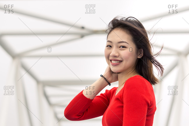 Pleased Asian young woman enjoying walk