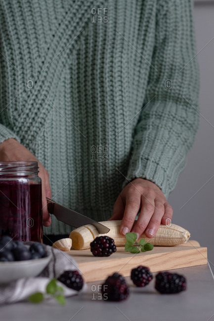 Crop person cutting with knife fresh banana on wooden cutting board while preparing healthy vitamin smoothie with blackberry and blueberry at home