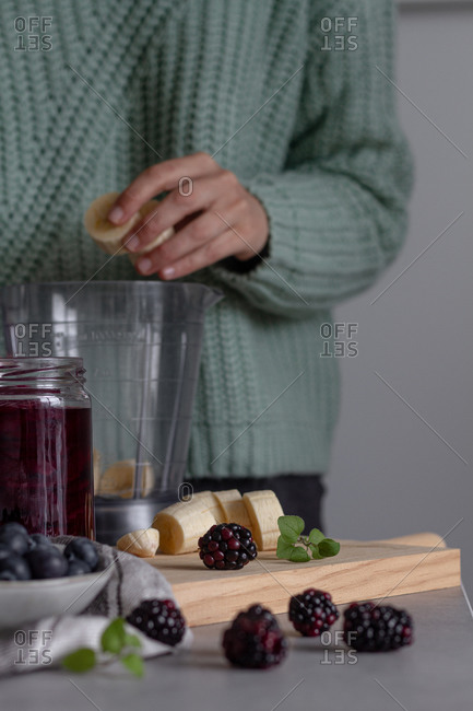 Cook preparing yummy drink of berry mix and mint in kitchen