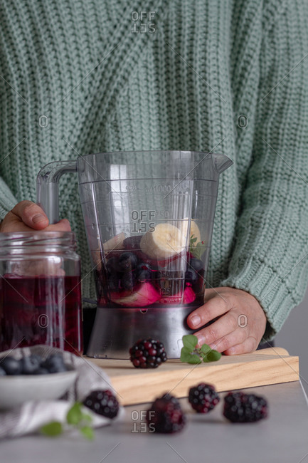 Crop person preparing healthy vitamin smoothie with banana and other berries in combination with mint using blender standing on wooden cutting board on table in modern kitchen