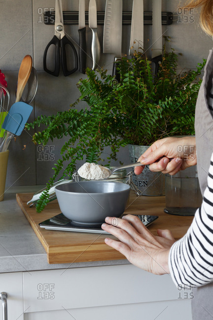Crop hands of faceless woman in apron adding spoon of flour into bowl on scale while cooking in modern kitchen