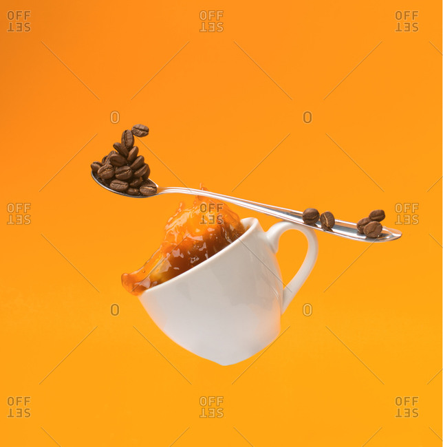 Falling white cup with splashing hot coffee and teaspoon with beans of coffee on yellow background