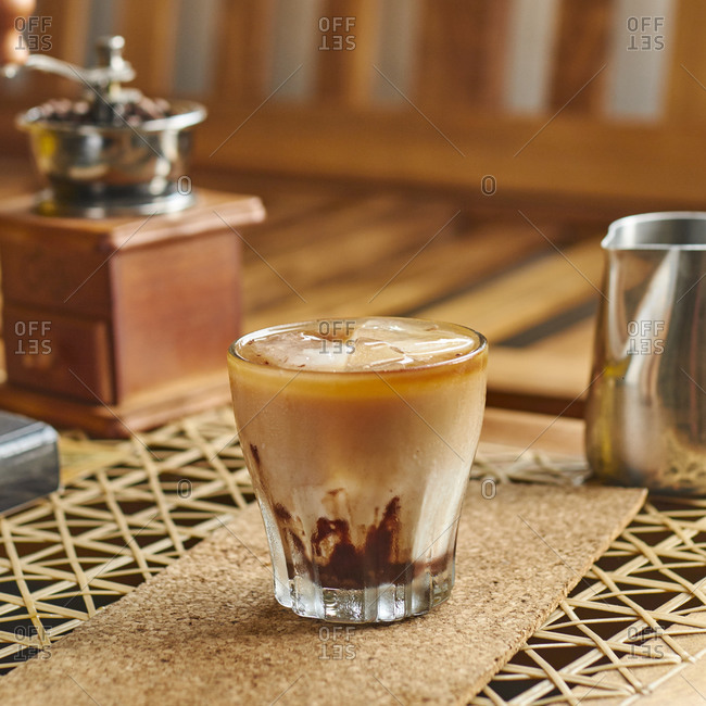 High angle of transparent glass of yummy coffee with fresh milk and ice standing on cork coaster beside small metal coffee pot and vintage grinder on brown wooden table at home