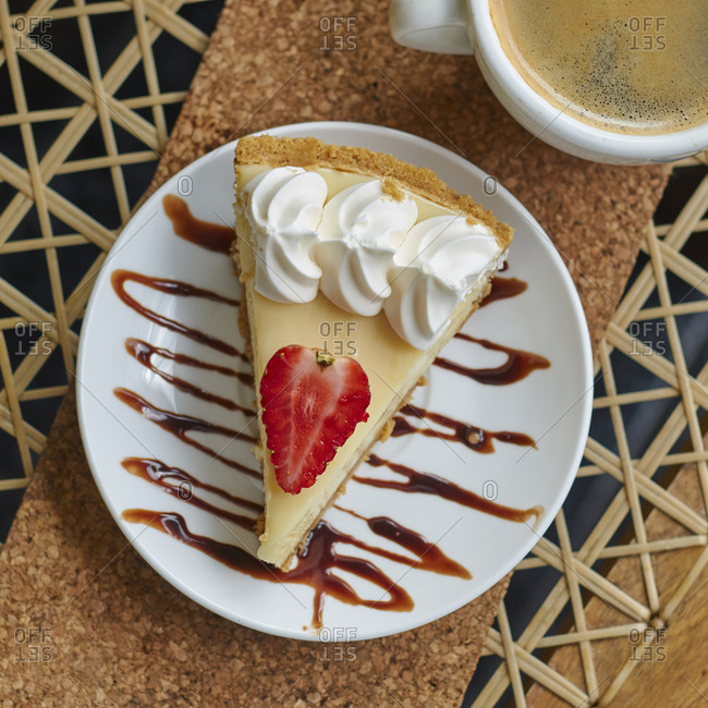 From above of plate with delicious cheesecake with strawberry and cream near cup of cappuccino on table