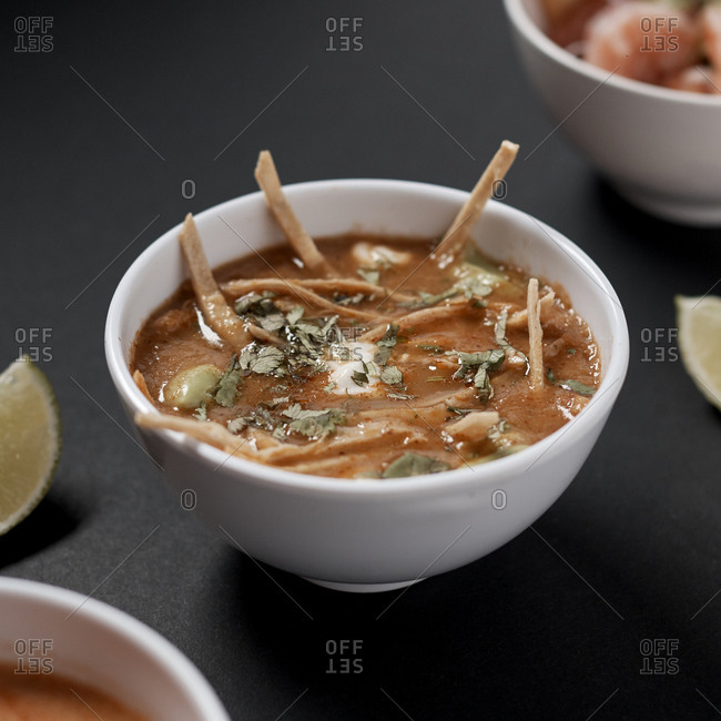 Bowl of tasty domestic vegetable soup with sour cream and fresh herbs