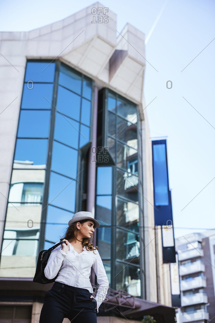 From below of glamorous young woman in white shirt and hat throwing black bag over shoulder and looking away at modern city street