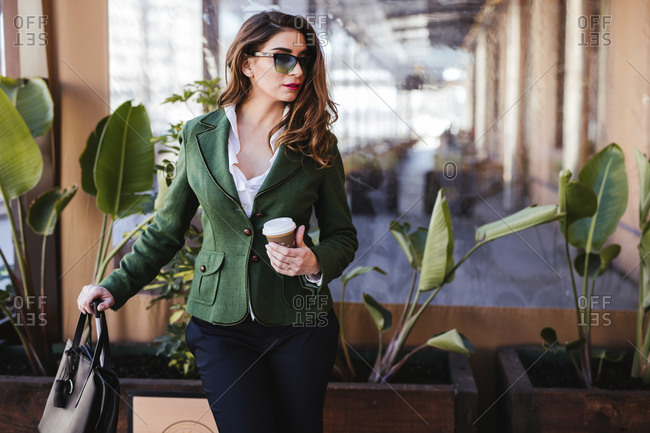 Trendy woman in fashionable clothing and sunglasses waiting for taxi with coffee to go and suitcase at city street