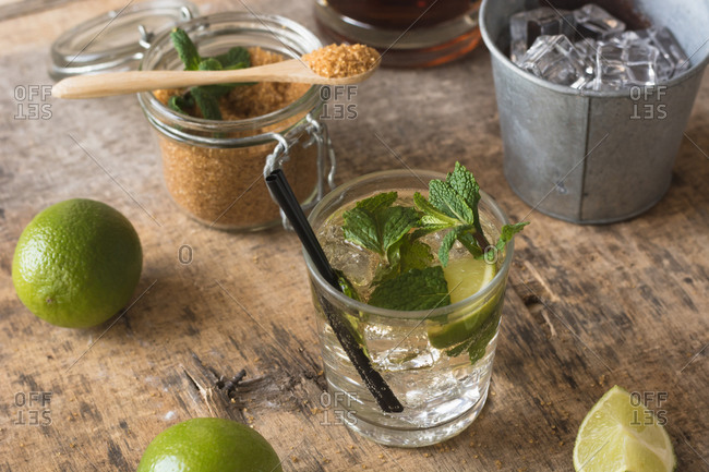Overhead fresh limes and peppermint leaves placed on napkin and table near rum and brown sugar for mojito preparation