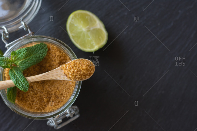 Overhead brown sugar in a jar near fresh limes and peppermint leaves placed on black background