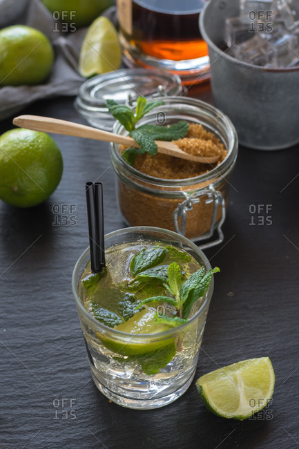 From above glass of cold mojito made of rum and lime with peppermint and brown sugar and placed on wet table near cubes of ice