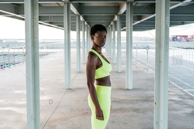 From below African American adult sportswoman in vibrant green activewear focusing standing alone along waterfront among metal columns under roof