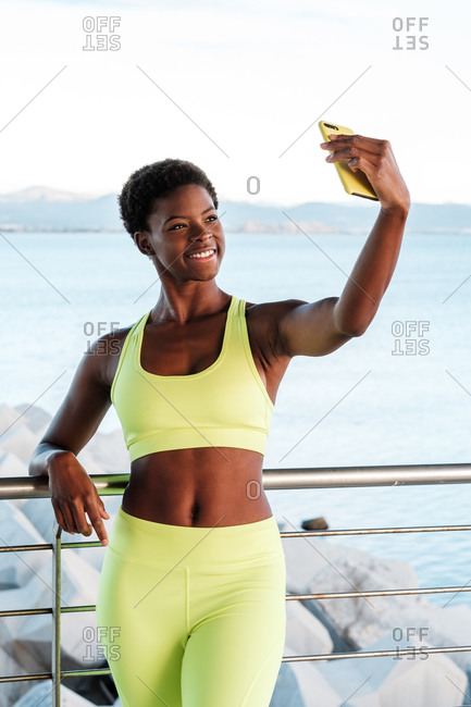 Fit confident African American female in vibrant yellow sportswear focusing on screen and taking selfie with smartphone while standing leaning on metal fence on promenade against blurred seascape