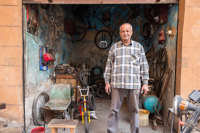 Cairo, Egypt - December 14, 2019: Ethnic calm aged male in casual wear standing at entrance to garage looking at camera