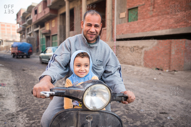 Cairo, Egypt - December 14, 2019: Glad ethnic man in casual wear riding on moped with daughter on road in old poor district and looking at camera