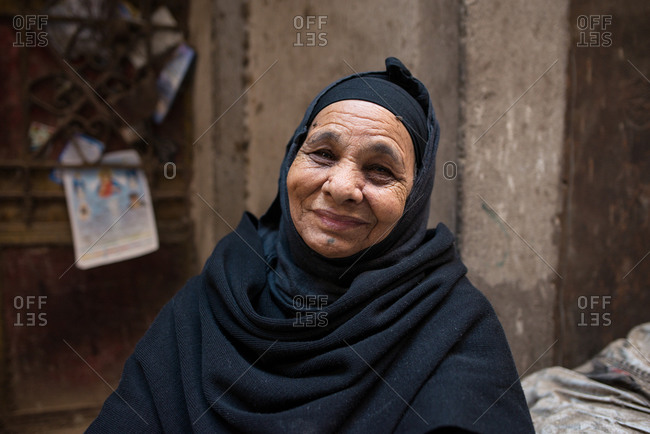 Cairo, Egypt - December 14, 2019: Positive aged lady with crossed arms in traditional Arabian wear sitting in street looking at camera