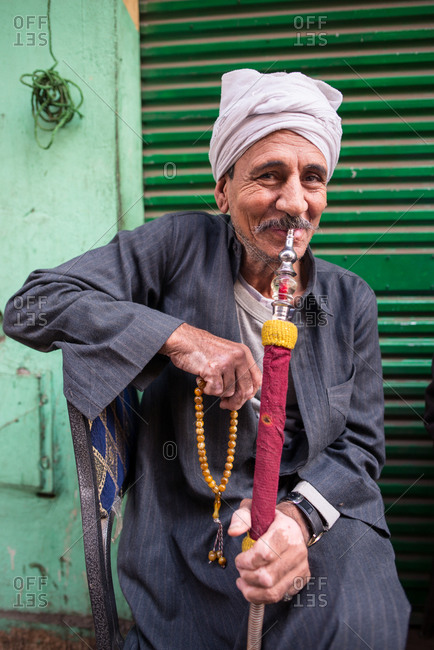 Cairo, Egypt - December 14, 2019: Group of calm adult ethnic man in traditional wear smoking hookah relaxing together sitting on chair in street of old city