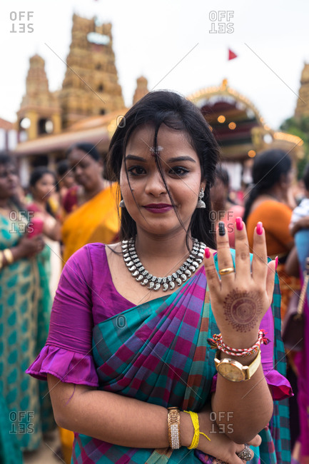 Jaffna, Sri Lanka - August, 9 2019: Young Tamil female in colorful traditional clothes looking at camera while standing against crowd and temple during Nallur Kandaswamy Kovil Festival