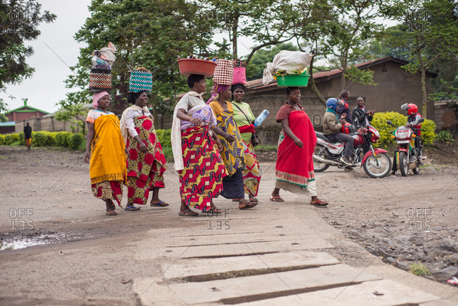 Ruanda, Africa  - December 14, 2019: African American women carrying bowls on heads walking in street of local poor town