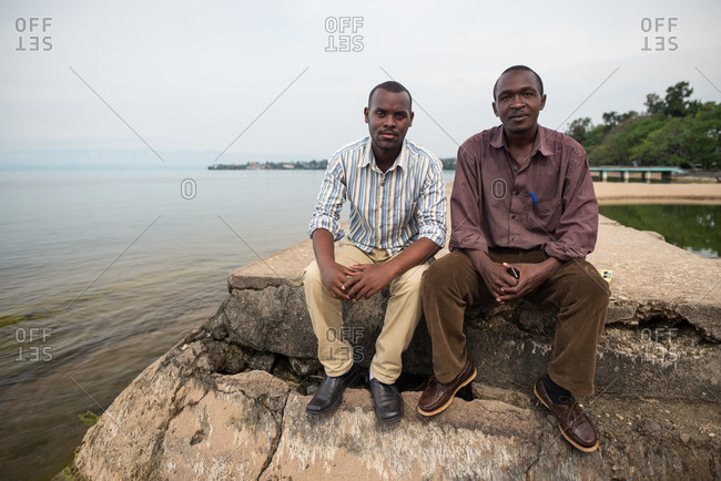 Ruanda, Africa - December 14, 2019: African American guy in casual wear resting with friend sitting on stone pier in seafront looking at camera