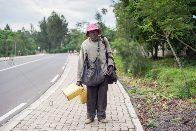 Ruanda, Africa - December 14, 2019: Homeless African American male with bags strolling on road of city looking at camera