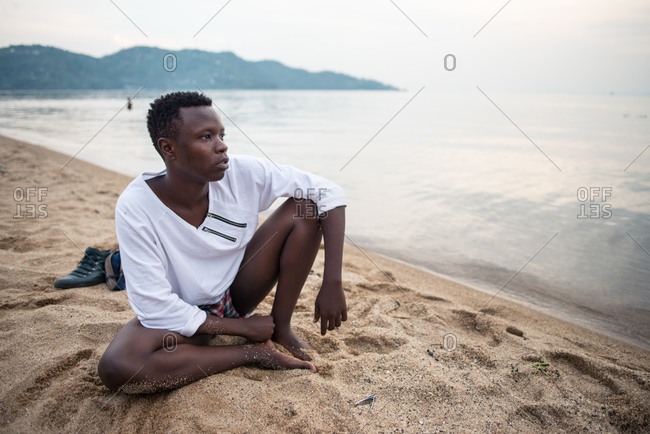 Ruanda, Africa - December 14, 2019: African American guy in casual wear resting sitting on sandy beach looking away thoughtfully