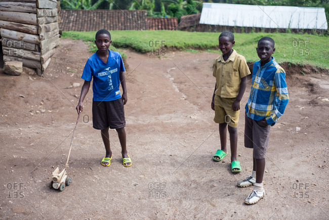 Ruanda, Africa - December 14, 2019: Group of smiling African teens in casual wear standing together on ground yard of village playing together and looking at camera