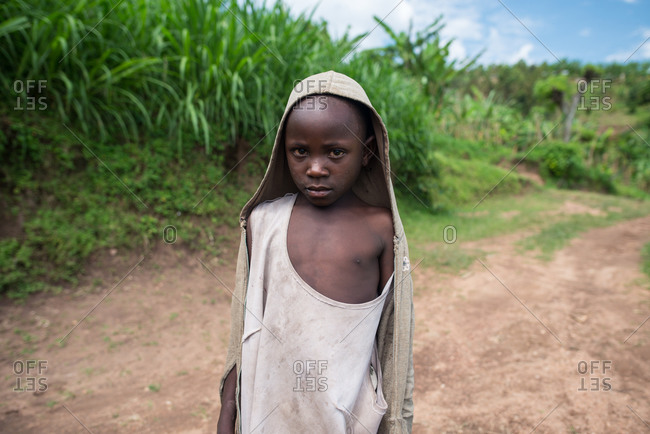 Ruanda, Africa - December 14, 2019: Miserable little African boy in dirty clothes walking on road in green rural land looking at camera