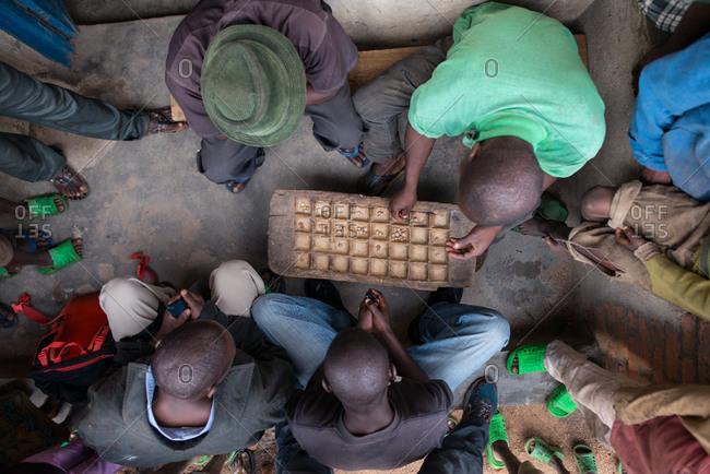 Ruanda, Africa - December 14, 2019: Group of focused African men playing board game sitting on street in village