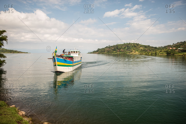 Ruanda, Africa - December 14, 2019: Small ship with group of black folks moored in water of river with tropical greens around