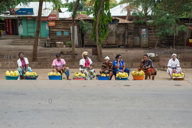 Tanzania, East Africa - November, 2016: African female bargainers sitting along road and selling fresh yellow bananas with wooden small houses on background in Tanzania