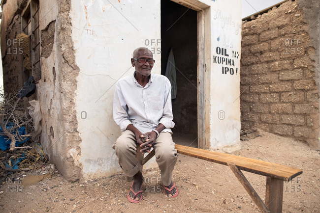 Tanzania, East Africa - November, 2016: Aged African man in sunglasses sitting on beach near old house