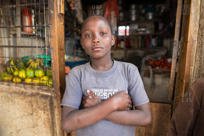 Tanzania, East Africa - November, 2016: African American boy in casual t shirt standing with crossed hands and looking at camera in doorway of small pantry at Tanzania at Africa