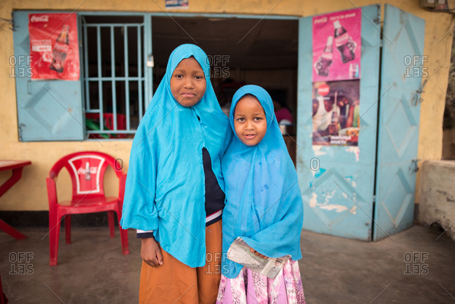 Tanzania, East Africa - November, 2016: Little African female local citizens in blue muslim head scarfs smiling and looking at camera in Tanzania