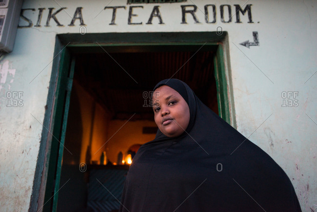 Tanzania, East Africa - November, 2016: From below of plump African woman in black hijab looking at camera with rocked building on background at Tanzania at Africa