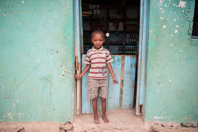 Tanzania, East Africa - November, 2016: Little African boy in casual clothing standing and looking at camera near small old house at city street of Tanzania