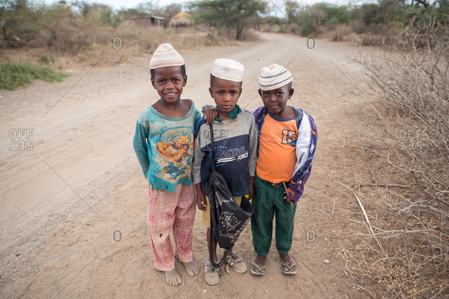 Tanzania, East Africa - November, 2016: Satisfied African little boys in traditional hats at countryside